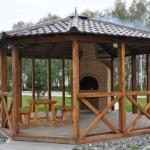 беседка с мангалом, построенная из древесины и увенчанная многоскатной шатровой кровлей